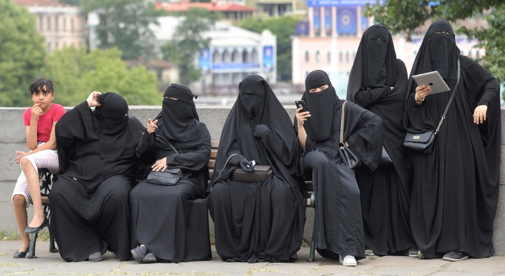 Foreign tourists wearing niqab have a rest on a bench in downtown Tbilisi on August 16, 2016. / AFP PHOTO / Vano Shlamov