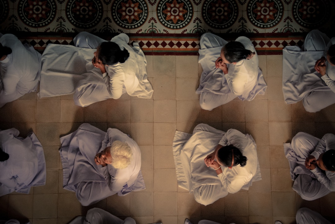 aerial_shot_of_people_in_white_robes_sitting_on_the_floor__praying__in_vietnam