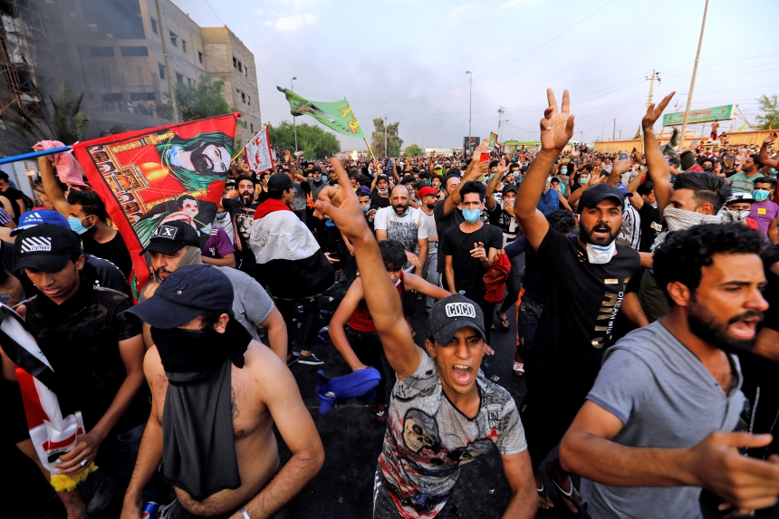 Image: Demonstrators gesture at a protest over unemployment, corruption and poor public services, in Baghdad