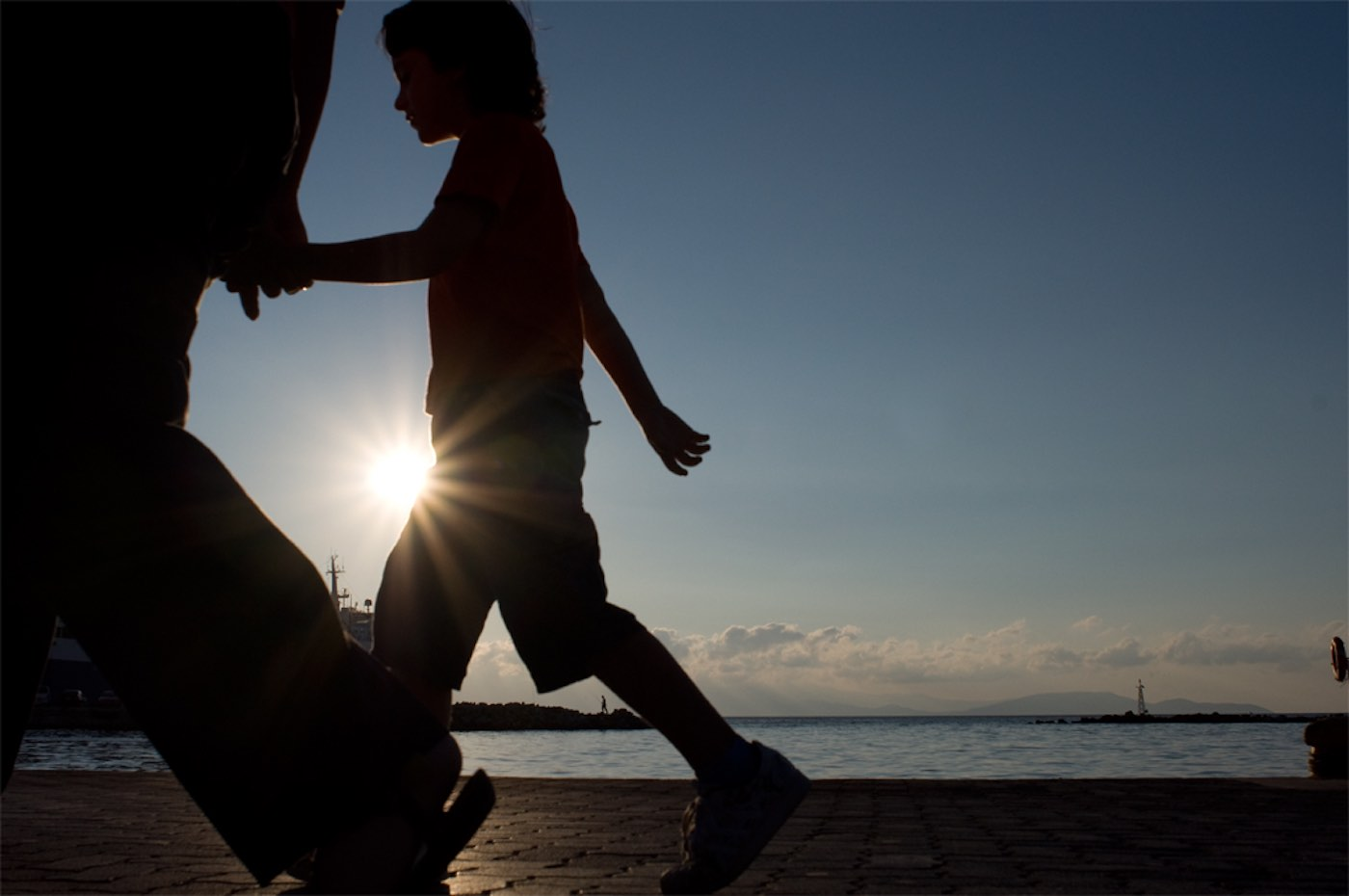 child-boy-walking-beach-holding-hands-family-sunset-silouette-cc-stefanos-papachristou.jpg